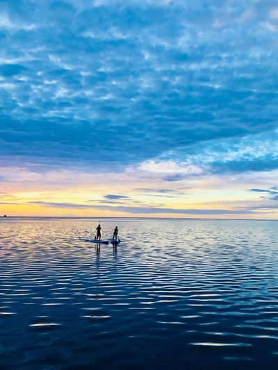 People Paddleboarding In Sea Against Sky During Sunset