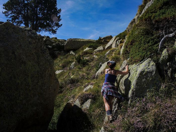 Rear View Of Woman Climbing Rocks On Mountain