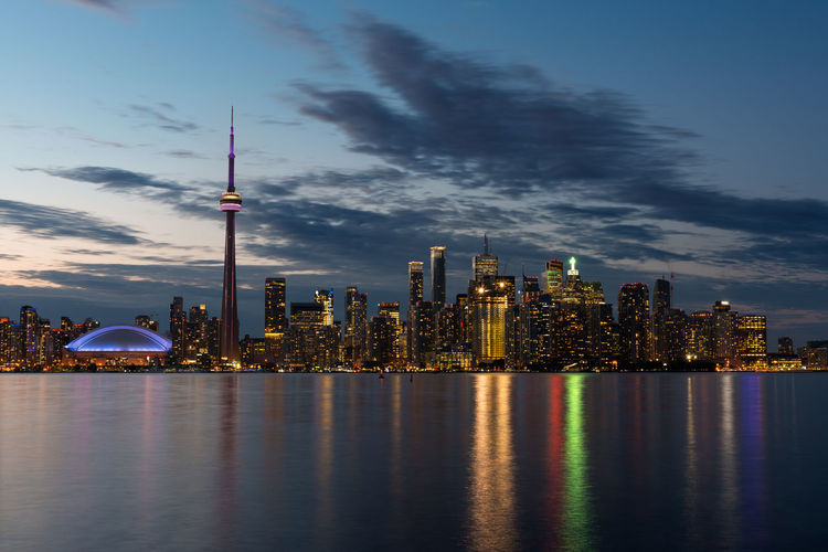 Scenic view of lake ontario in illuminated city against sky