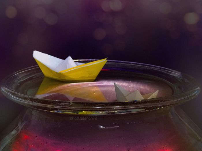 Close-up of paper boats floating on water in container