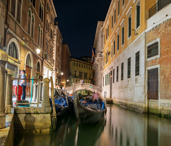 Gondola on a canal amidst buildings in city at night