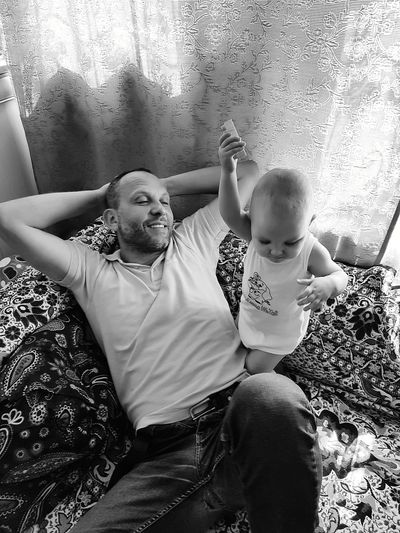 High Angle View Of Father And Son Sitting On Bed At Home