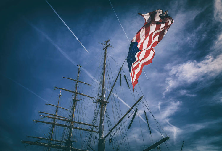 Low angle view of american flag waving on mast against cloudy sky
