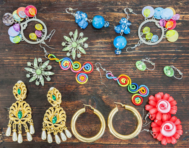 Directly above view of various earrings on wooden table