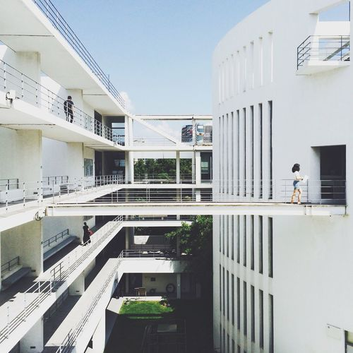 People Walking On Building In University Against Clear Sky