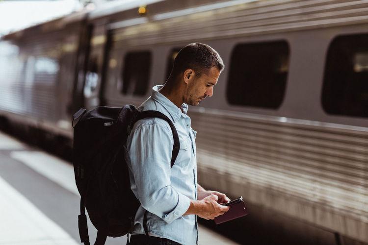 Man using mobile phone at railroad station