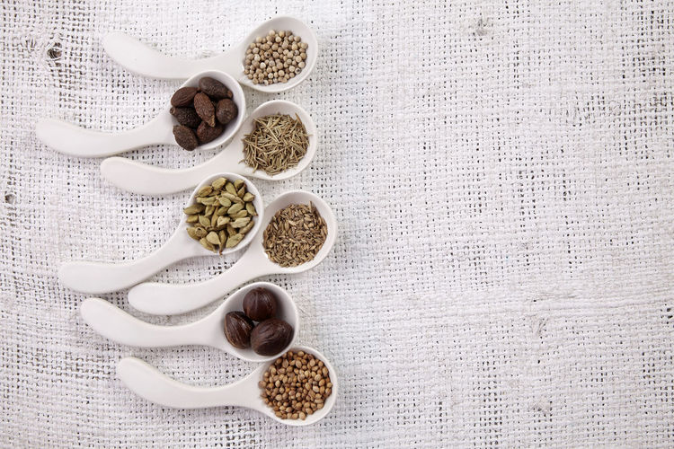 arrangement of spices on the white background Burlap Choice Herb Rosemary Spoon Arrangement Assortment Cardamom Condiment Coriander Cumin Fenugreek Ground - Culinary Group Of Objects High Angle View Ingredient Malva Nut - Food Nutmeg Pepper Sackcloth Season  Spice Variation Variety