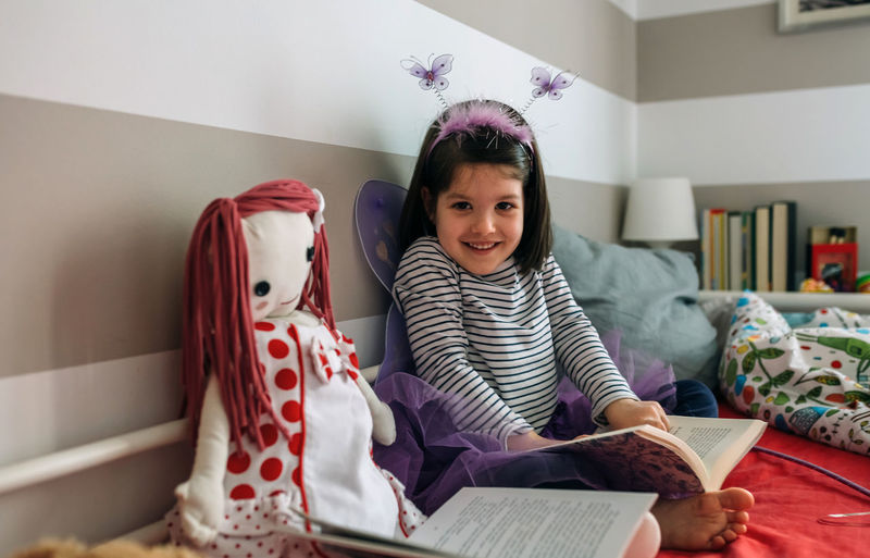 Little girl looking at camera disguised as a butterfly sitting on the bed next to her doll reading a book each Bed Children Doll Happy Home Horizontal Imagination Lifestyle Peace Reading Toys Bedroom Book Butterfly Child Childhood Colorful Concentration Culture Girl Indoors  One Person Pajamas Pijama Striped