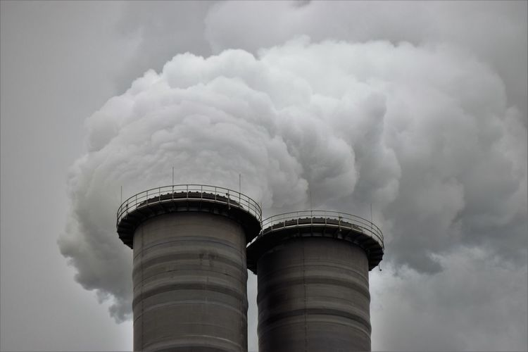 Low Angle View Of Factory Emitting Smoke Against Sky