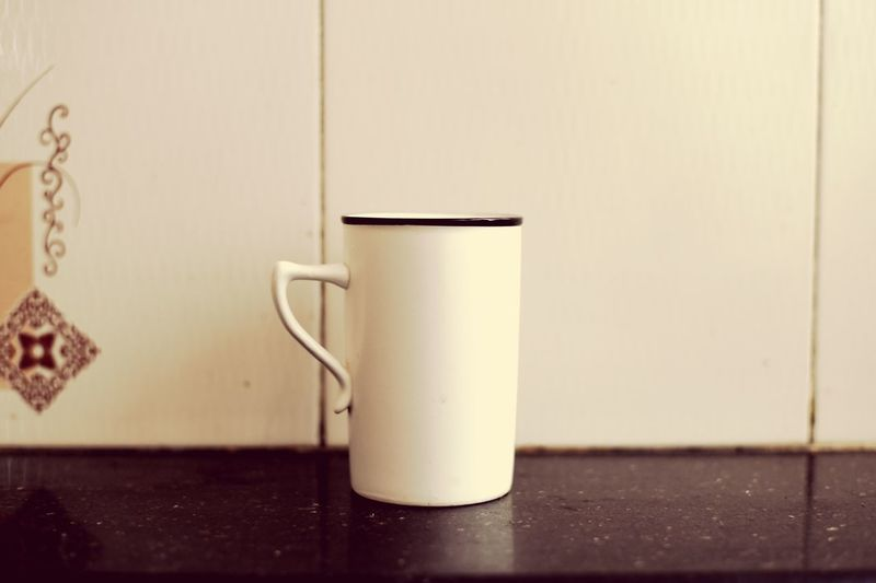 Close-up of coffee cup on table against wall