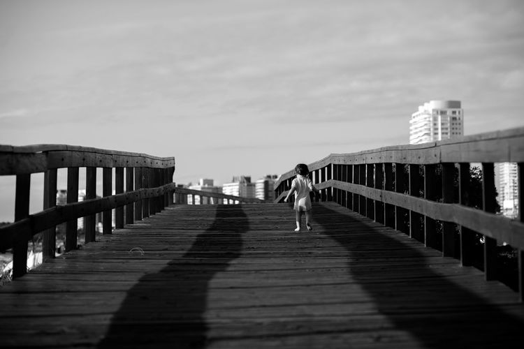 Rear view of child walking on footbridge