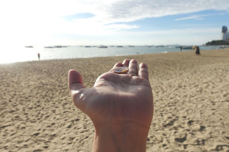 Midsection of person on sand at beach against sky