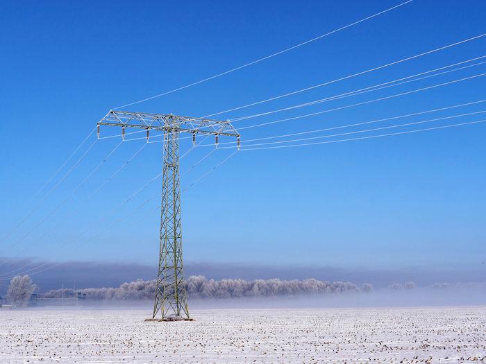 Electricity pylon on land against clear blue sky