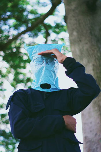 Low angle view of man wearing plastic bag while standing against tree