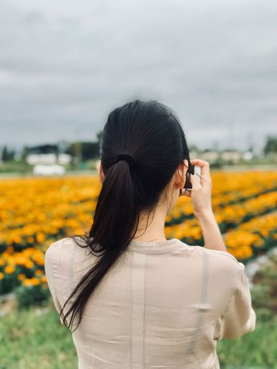 Rear view of young woman photographing with mobile phone while standing on field against cloudy sky