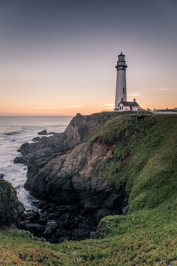 Pigeon Point Lighthouse On Cliff By Sea Against Sky During Sunset