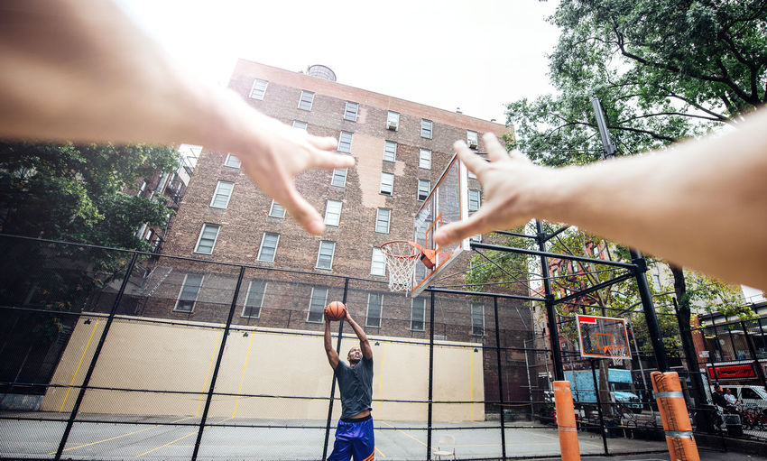 Cropped hands of person against man playing basketball at court