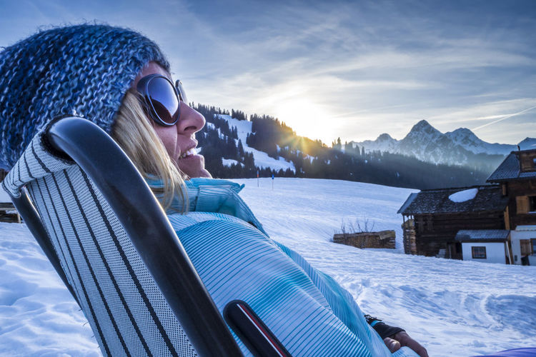 Woman relaxing in deck chair after skiing Alps Apres Ski Chair Deck Chair Enjoying Life Holiday Ischgl Lifestyles Moment Montafon Mountain Outdoors Recreation  Relaxing Ski Skiing Sports Sun Sunset Sölden Unfiltered Vacations Wellness Winter Woman