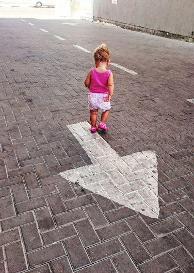Rear View Of Girl Walking Over Arrow Symbol On Cobblestone Street