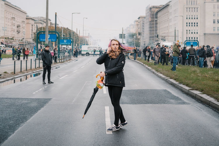 Woman on road in city against sky