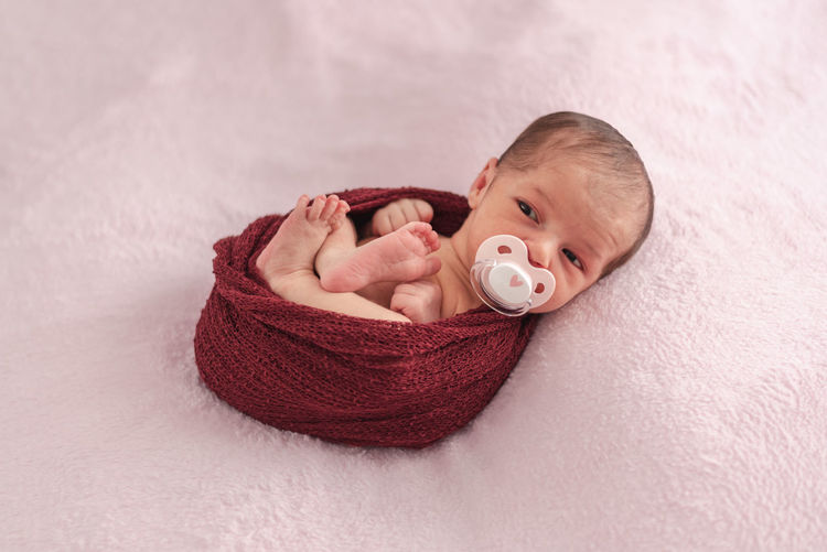 Newborn baby with pacifier tucked in a ball of wool. newborn session concept