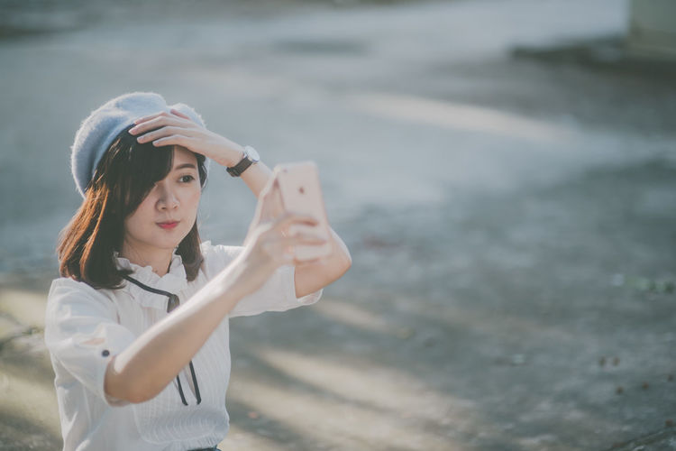 Camera - Photographic Equipment Casual Clothing Childhood Day Focus On Foreground Holding Leisure Activity Lifestyles One Person Outdoors Photo Messaging Photographing Photography Themes Real People Selfie Standing Technology Wireless Technology Young Adult Young Women