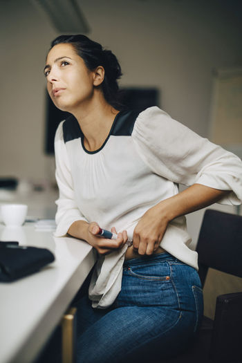 Mid adult woman sitting on table