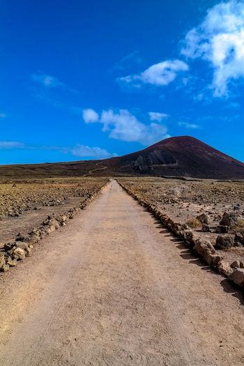 Road leading towards desert against blue sky