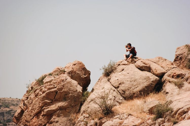 Young man sitting on rock against clear sky