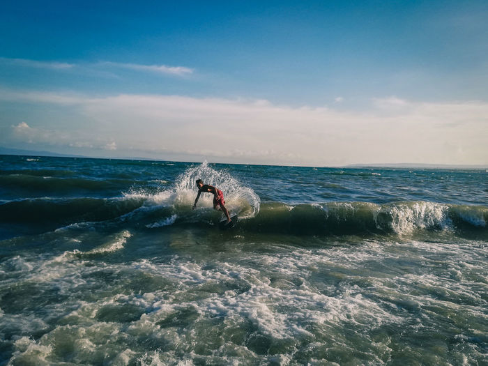 Young man surfing on sea against sky
