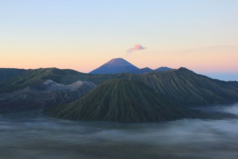 View of bromo and semeru mountains against sky during sunrise. it's savana is covered by the mist.