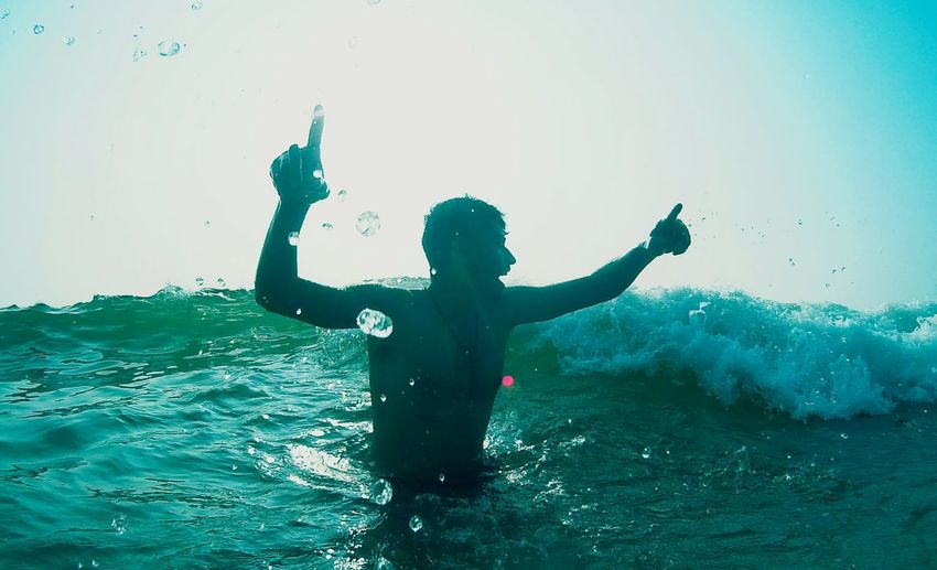 Low angle view of man with arms raised enjoying in sea against sky on sunny day