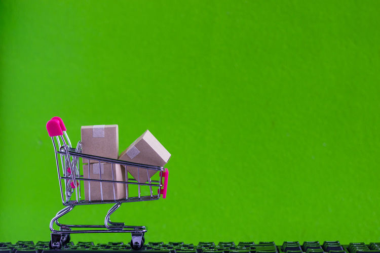Close-up of small shopping cart with packages on keyboard against green wall