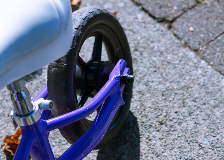 The back of a kids strider bike. Children Kids Bike Strider Bike Bike Bikini Cement Background Close Up Close-up Day Full Frame No People Outdoors Playing Purple Bike Running Bike Tire Transportation