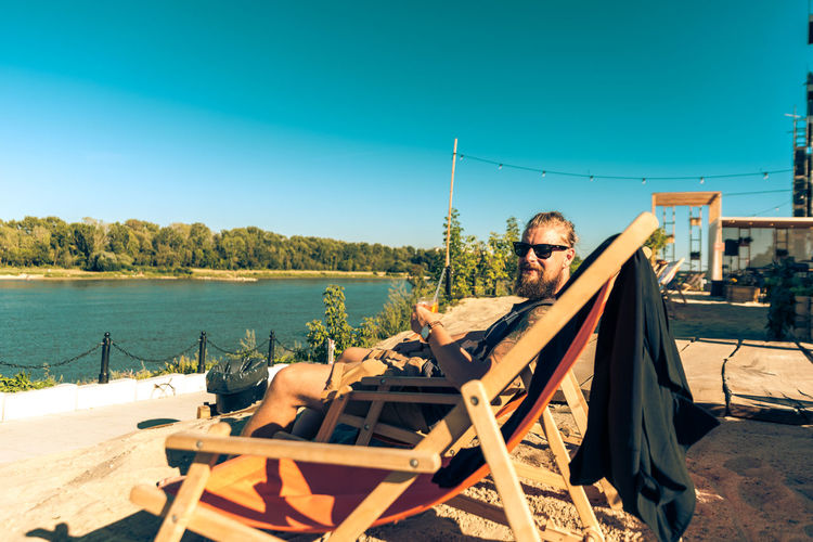 Hipster sitting on folding chair at riverbank against clear blue sky