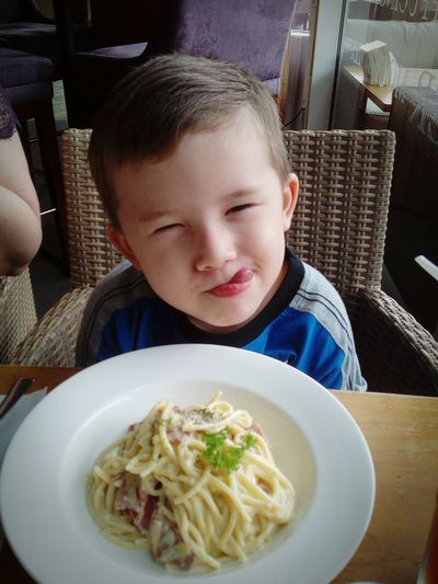 Cute boy sticking out tongue while having noodles at restaurant