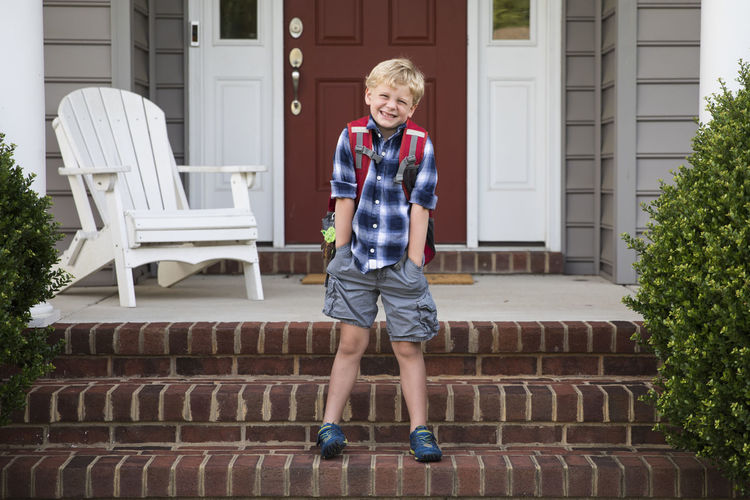Full length portrait of boy standing against building