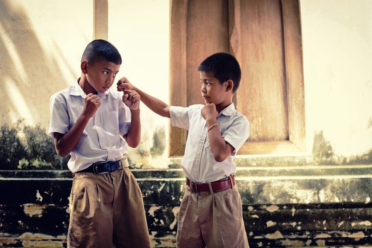 Two asian boys wearing school uniforms are playing boxing, old wall temple background Local Thailand Asian  Boxing Student Thailand Wall Boy Old Buildings Playing