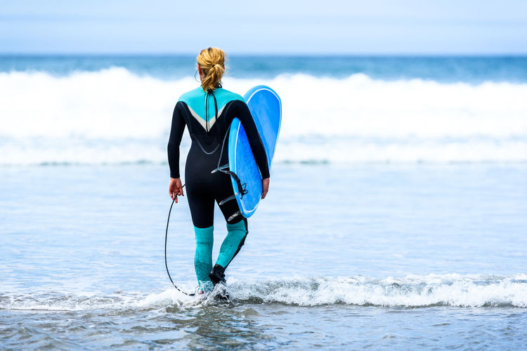 Rear View Of Woman With Surfboard Walking At Beach