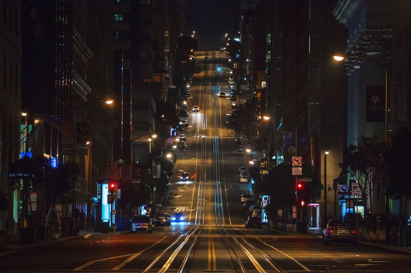 Road amidst buildings at night