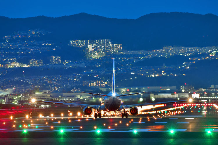 Airplane landing on runway in illuminated city against sky at night