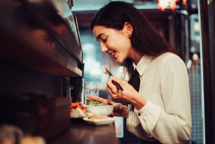 Side view of young woman using mobile phone in restaurant