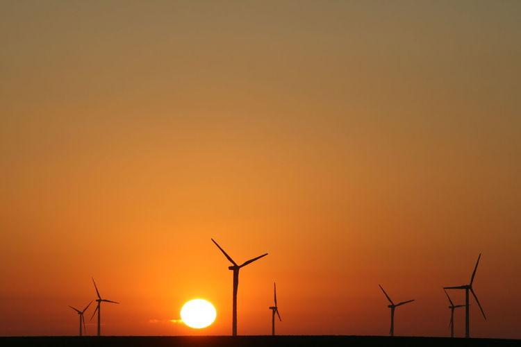 Silhouette of wind turbines on landscape