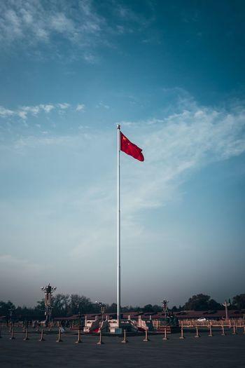 Flags on beach against blue sky