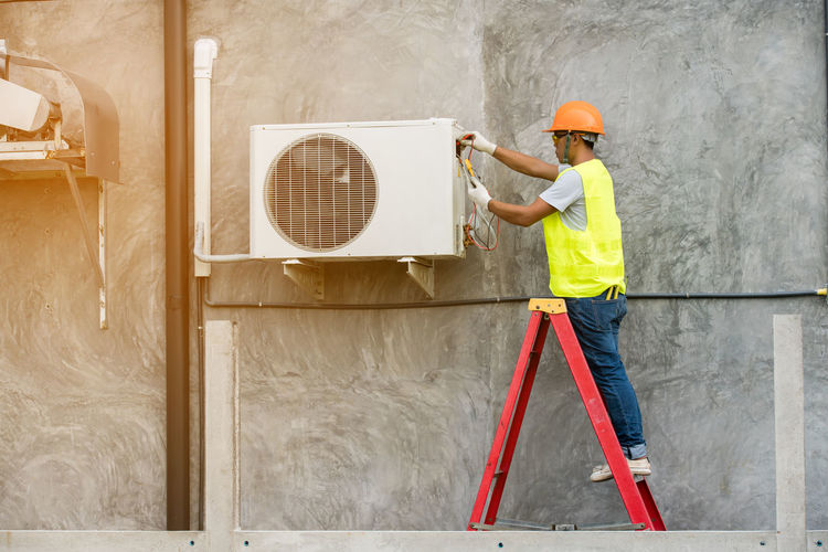 Side View Of Man Repairing Air Conditioner