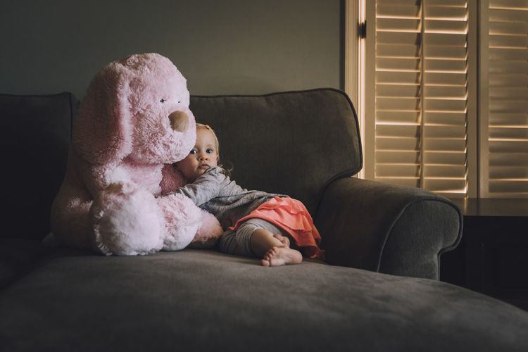 Portrait of girl with teddy bear on sofa at home