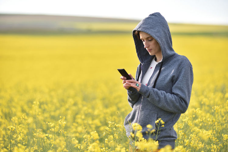 Woman Holding Phone While Standing On Field