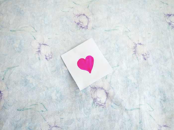 Directly Above Shot Of Paper With Pink Heart Shapes On Bed