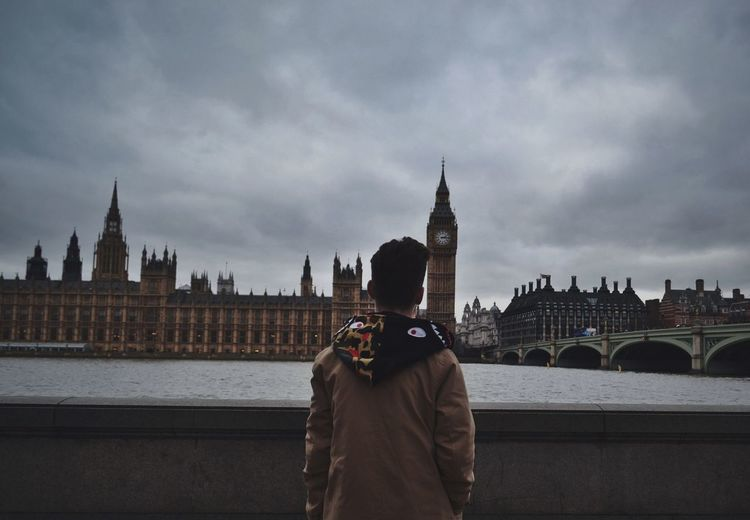 Rear View Of Man Looking At Big Ben Against Cloudy Sky