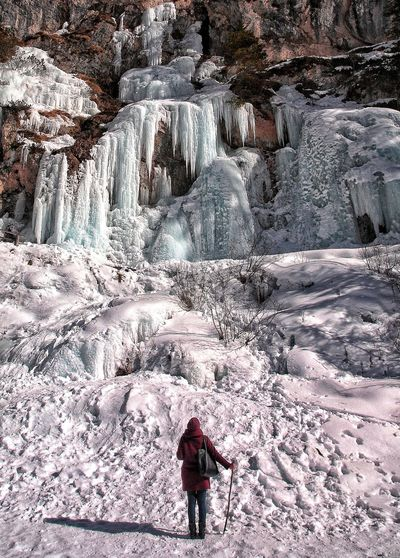 Full length of person standing on rock in winter
